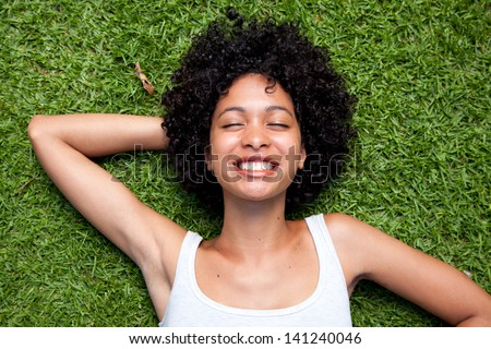 Happy mixed race woman lying down on green grass with hands behind her head. - stock photo