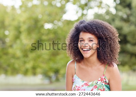 Happy mixed reac woman laughing joyfully in a green park - stock photo