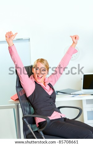 Happy modern business woman sitting at workplace rejoicing success - stock photo