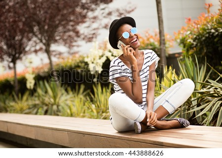 happy modern young student black woman with sunglasses, hat striped shirt using her cellphone outside in park or university