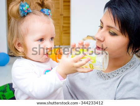 Happy mom and baby girl drinking from bottle. The concept of childhood and family. Beautiful Mother and her baby - stock photo
