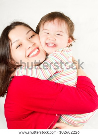 Happy mom and baby girl hugging and laughing - stock photo