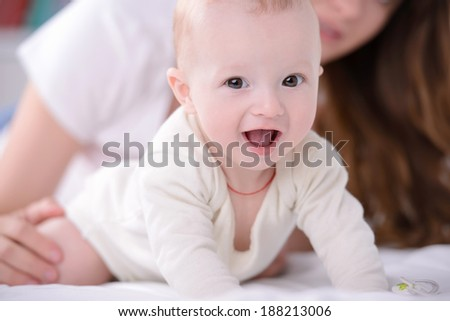 happy mom and baby playing on the bed at home - stock photo