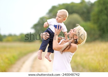 Happy Mom and baby son in summer nature - stock photo