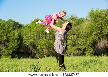 Happy mom and child girl hugging on nature The concept of childhood and family. Beautiful Mother and her baby outdoors - stock photo