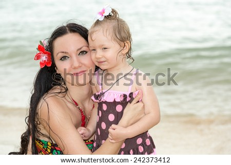 Happy mom and child girl hugging on tropical beach. Sea, water and family background - stock photo