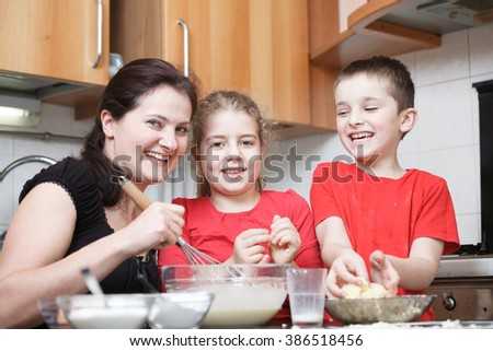 happy mom and kids in the kitchen making dough mixing flour, milk, eggs in a glass bowl  - stock photo