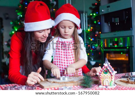 Happy mom and little girl in Santa hat baking Christmas gingerbread cookies together - stock photo