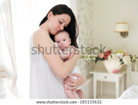 Happy mom gently hugs the baby in a light room - stock photo