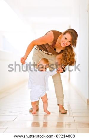 Happy mom helping baby to walk - stock photo