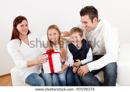 Happy mom receiving a gift from her kids at home - stock photo
