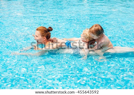 Happy mom with children in swimming pool - stock photo
