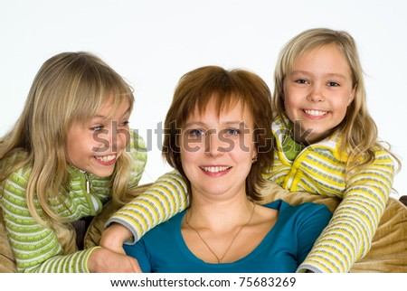 happy mom with daughters on sofa on white - stock photo