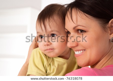 happy mom with her sleeping baby on sofa