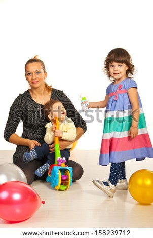 Happy mom with two kids playing with toys and balloons - stock photo