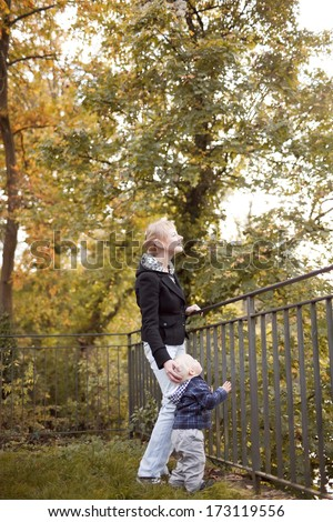 Happy moments: little boy with mother on outdoor walk in autumn park.