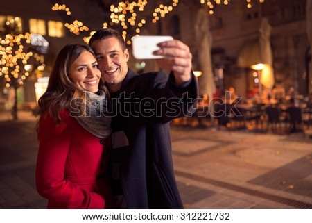 happy moments together. Happy young loving couple making selfie and smiling while standing Christmas background - stock photo