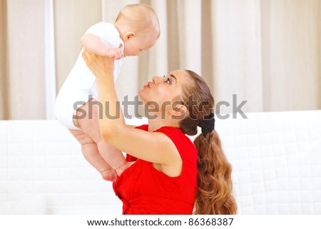 Happy mommy holding smiling adorable baby in hands and playing - stock photo