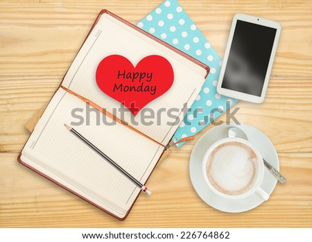 Happy monday on notebook with smart phone and coffee cup on wood - stock photo