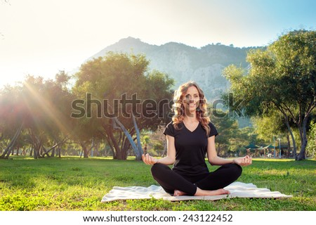 Happy morning yoga. Cheerful Young woman in lotus pose in the park with mountains view. Practicing yoga with trees and sun ray in the background - stock photo
