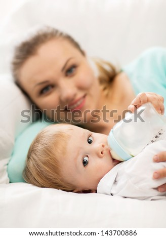 happy mother and adorable baby with feeding-bottle