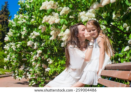 Happy mother and adorable girl enjoying warm day in lush garden - stock photo