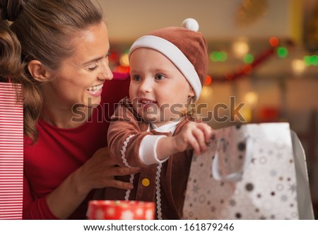 Happy mother and baby checking christmas shopping bags - stock photo