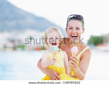 Happy mother and baby eating ice cream - stock photo