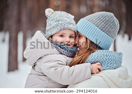 happy mother and baby girl having fun on the walk in winter snowy forest - stock photo