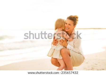 Happy mother and baby girl hugging on beach at the evening - stock photo