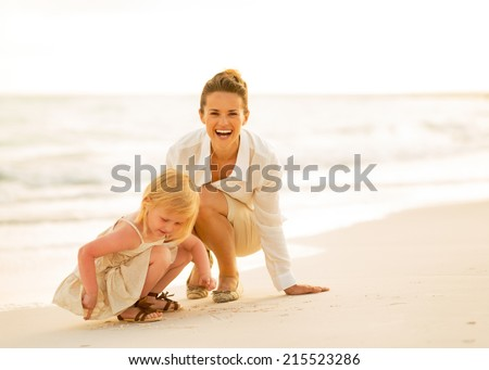 Happy mother and baby girl playing on the beach in the evening - stock photo