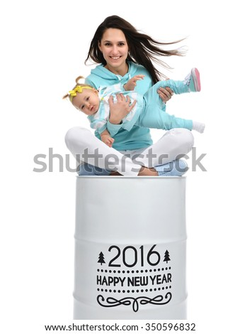Happy mother and baby girl sitting on big barrel roll with christmas new year sigh isolated on a white background - stock photo