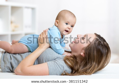 Happy mother and baby hug and play lying indoors - stock photo