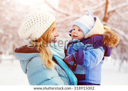 happy mother and baby in winter park. family outdoors. cheerful mommy with her child - stock photo