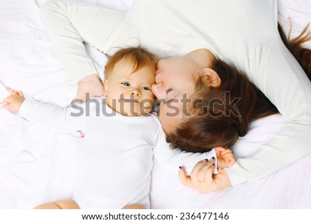 Happy mother and baby lying on bed at home, top view - stock photo