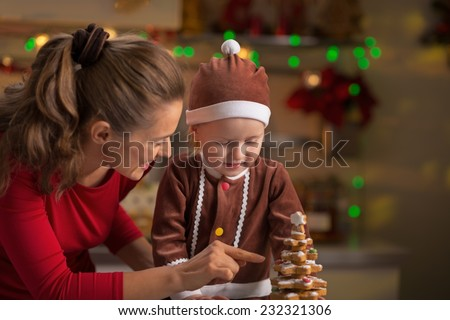 Happy mother and baby making christmas tree from cookies - stock photo