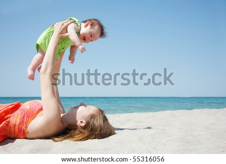 happy mother and baby playing on beach - stock photo