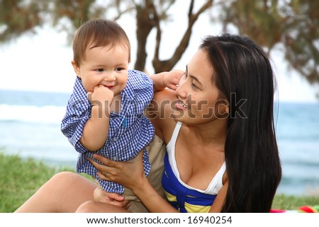 happy mother and baby playing outdoors - stock photo