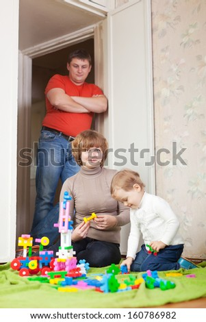 Happy mother and baby plays with toys in home. Focus on woman only - stock photo
