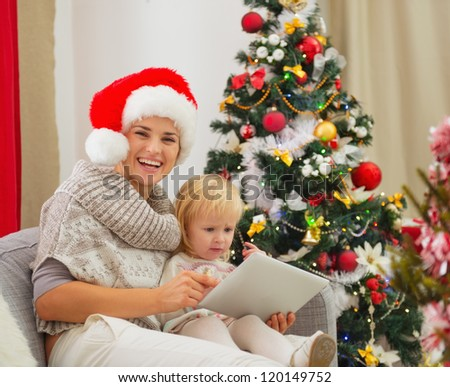 Happy mother and baby using tablet PC near Christmas tree