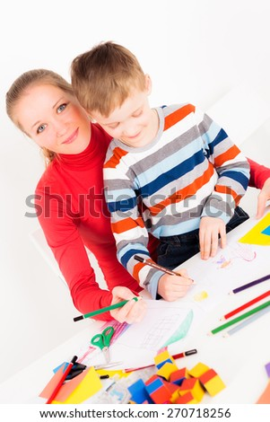 Happy mother and child drawing together