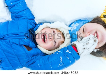 Happy mother and child lying on the snow in winter park and play - stock photo
