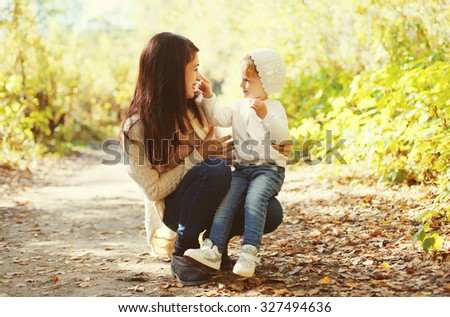 Happy mother and child playing together in autumn park - stock photo