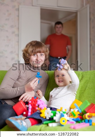 Happy mother and child plays with toys in home - stock photo