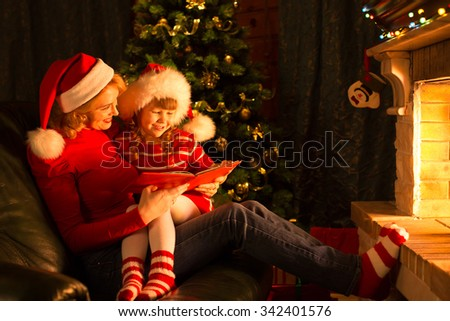 Happy mother and child reading book at fireplace in christmas decorated living room  - stock photo