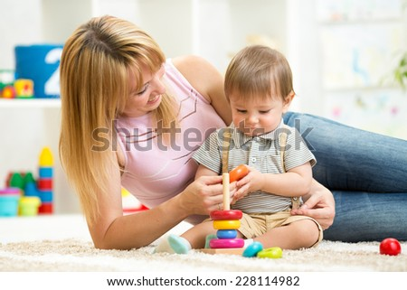 happy mother and child son playing together indoor at home - stock photo