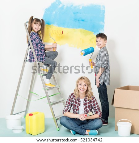 Happy mother and children  at home. Smiling girl and boy painting wall of room. Smiling family painting big Ukrainian flag on wall at home.