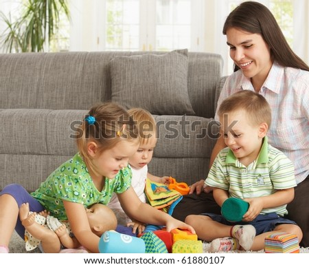 Happy mother and 3 children sitting on floor at home playing together smiling.? - stock photo