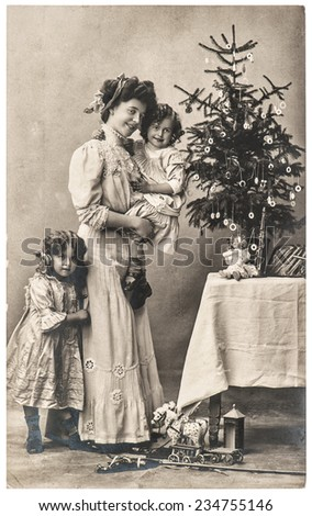 happy mother and children with christmas tree and antique toys. vintage sepia picture with original film grain and blur - stock photo