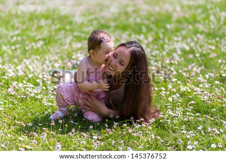 Happy mother and daughter are lying on grass in the park - stock photo